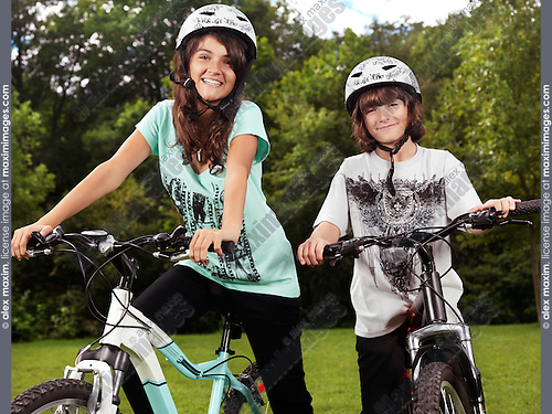 Two happy smiling children in cycling helmets on their bicycles in a park, brother and sister, 10 and 13.