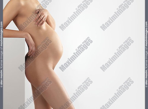 Beautiful naked pregnant woman side view isolated on gray background