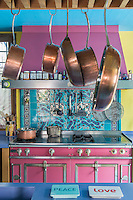 A pink cooking range and matching extractor dominates one wall of the kitchen which also features a rack of copper pans hanging above the central kitchen island