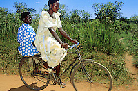 Uganda. Kayunga district. Gayaza. Two young women ride a bicycle on the dirt road. Both girls wear nice dresses.© 2004 Didier Ruef