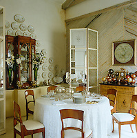 A collection of porcelain hangs on the wall and is displayed in a glass-fronted cabinet in this elegant dining room