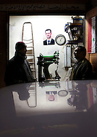 A portrait of Bashar al-Assad hangs on the wall of a small shop while two people talk at the entrance in the Old City of Damascus. Protests against the ruling Baathist regime of Bashar al-Assad erupted in March 2011. Although they were initially peaceful,  they were violently repressed by the Syrian army and police. In response to being ordered to shoot unarmed civilians, large numbers of men deserted the army and formed the Free Syrian Army. The protest movement has now turned into an armed uprising with clashes between the regular army and the Free Syrian Army taking place in early 2012....