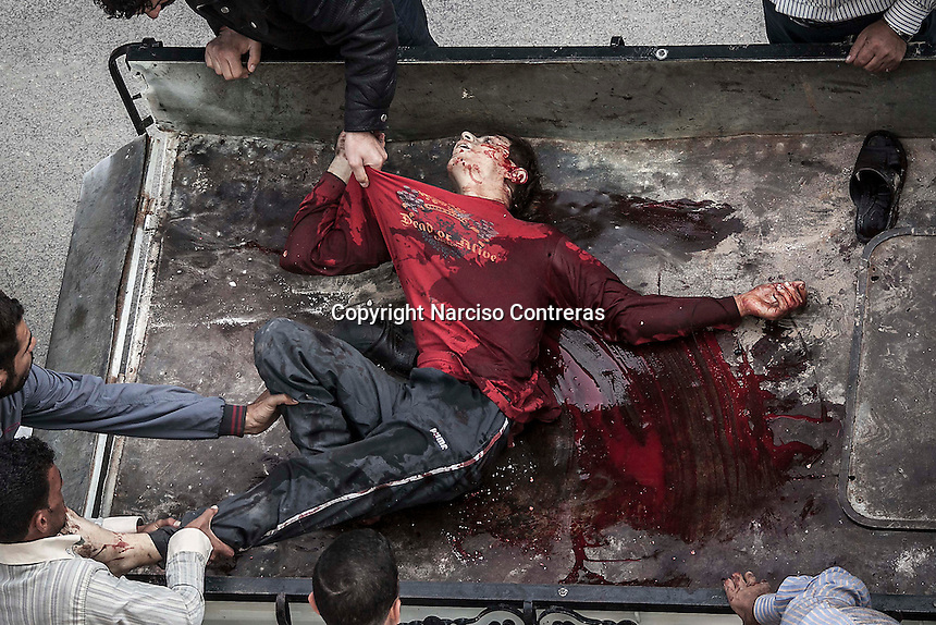 In this Tuesday, Oct. 23, 2012 photo. A Syrian civilian is dragged out from a truck as he arrives dead at one hospital in Tarik Al-Bab after was killed by mortar shelling while he was buying bread at a bakery in Hananu district, at the northeast of Aleppo City. (AP Photo/Narciso Contreras).