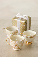 Three candles in decorative cups beside a gold-wrapped parcel