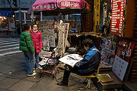 Newspaper vendor reading one of his magazine..Shanghai, February 2006.