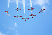 Snowbirds acrobatic team formation in line with smoke on against blue sky