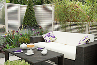 Modern sophisticated upscale patio with black and white color theme, fence, evergreens in raised beds, black leaved plants, bamboo, fence wall, tea service on table, sofa couch lounge for a beautiful room outdoors in home landscaping