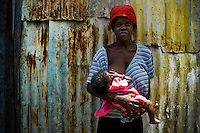 A young Haitian mother feeds her baby in the slum of Cité Soleil, Port-au-Prince, Haiti, 24 July 2008. Cité Soleil is considered one of the worst slums in the Americas, most of its 300.000 residents live in extreme poverty. Children and single mothers predominate in the population. Social and living conditions in the slum are a human tragedy. There is no running water, no sewers and no electricity. Public services virtually do not exist - there are no stores, no hospitals or schools, no urban infrastructure. In spite of this fact, a rent must be payed even in all shacks made from rusty metal sheets. Infectious diseases are widely spread as garbage disposal does not exist in Cité Soleil. Violence is common, armed gangs operate throughout the slum.