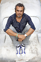 Subodh Gupta, contemporary artist with one of his sculptures outside his recently completed studio in Gurgaon, a satellite town of Delhi...Gupta's most celebrated sculptures are constructed from common domestic items including the steel pots and pans that are a feature every Indian home. Of the kitchen-ware that forms the basis of his work, Gupta says,..&quot;The poor, the middle class and the rich use it at home. In this country, how many people have the utensils but they starve because there is no food?&quot;..Gupta was brought up, one of six children, to a railway-worker father in a north Indian village. ..Gupta's work fetches such huge sums of money. Two versions of his Mind Shut Down, modeled on the human skull and constructed entirely of steel kitchen utensils recently sold for EUR1 million each...Photo: Tom Pietrasik.Gurgaon, Haryana. India. .July 23rd 2009
