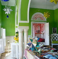 Over the study table which is covered in a colourful silk patchwork the eye leads to an orange-painted ante-room