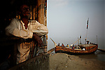 a man in a tea-house looks out at the meghna river and the human-traffic of a fishing-port on the eastern shore of Bhola.?This area in the south of Bangladesh has been called ground zero of climate-change due to heavy river and ocean erosion. The lowlying area is also hugely affected by cyclones and rising sea-levels...By the Mouth of Ganges, at the Bay of Bengal is the Island of Bhola. This home of about two million people is considered to be ground zero of climate change. Half the island has disappeared in the past 40 years, and according to scientists the pace is not going to slow down. People pack up and leave as the water get closer. Some to a nearby embankment, while those with enough money move further inland, but for most life move on until the inevitable. It's always about survival for the people in one of the worlds poorest countries...Photo by: Eivind H. Natvig/MOMENT