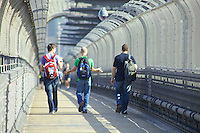 Pedestrians walking across Sydney Harbour Bridge.  The barbed security fencing prevents people from accessing the roadway, or jumping off the bridge