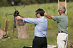 Former Minnesota Gov. Tim Pawlenty, left, and his brother, Dan Pawlenty shoot handguns while campaigning for the GOP presidential nomination at a gun range in Madrid, Iowa, July 20, 2011.