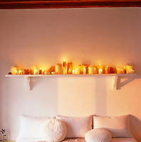 A simple shelf above this bed is lined with a collection of lit candles