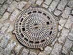 An iron manhole cover in a cobblestone street of Veliko Tarnovo, Bulgaria