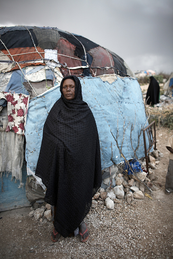 A woman stands outside her home in the Kililka Shanad camp for displaced persons on the outskirts of Hargeisa, Somaliland. Thousands fled to Ethiopia during the civil war in 1988 and returned in 1991 to find they no longer had homes..