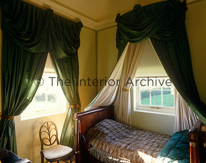 The single Empire bed in this small bedroom is dominated by a a pair of dark green silk curtains, one of which doubles as a bed hanging