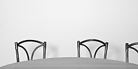 Two and a half chairs positioned behind a long table