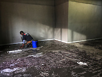 Worker prepares a floor for finishing as a business in Uptown gets a makeover.