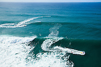 An aerial image of waves rushing towards the North Shore of O'ahu, with jet skiers towing surfers into the big waves.