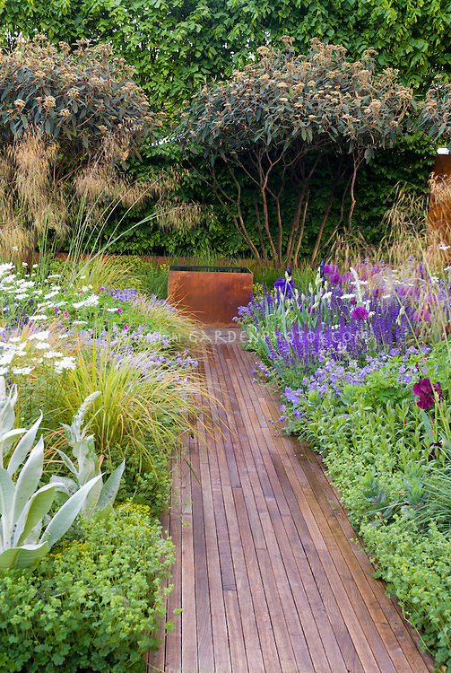Garden path of wood flanked by pretty flower border with