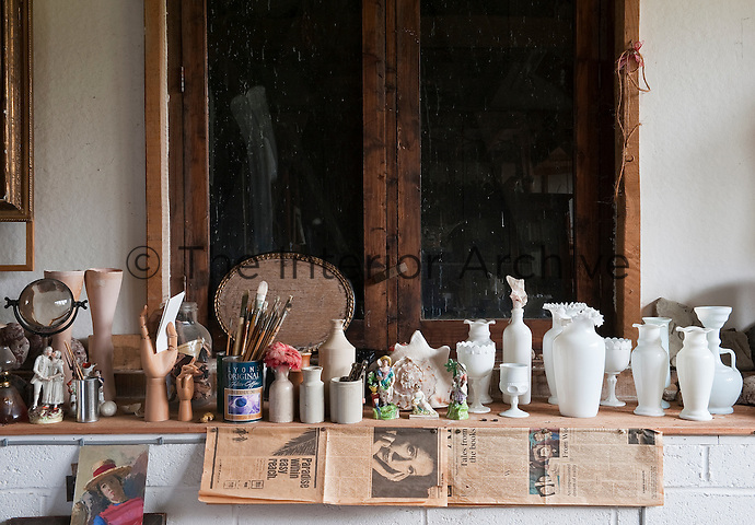 A fascinating jumble of miscellaneous objects is displayed on a long wooden shelf