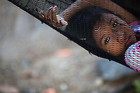 Soe, a 8 year old daughter of fisherman from Myanmar rests in a hammock outside her family home in Ban Nam Khem December 13, 2014. Ban Nam Khem, a small fishing village on Thailand's Andaman Sea coast, lost nearly half its 5,000 people in tsunami on December 26, 2004. Thailand prepares to mark the tenth anniversary of 2004 tsunami, the deadliest on the record, that killed at least 226,000 people in 13 Asian and African countries. In Thailand, over 5300 people were killed, including several thousand foreign tourists, when the waves swamped six coastal provinces, turning some of the world's most beautiful beaches into mass graves.  REUTERS/Damir Sagolj (THAILAND)