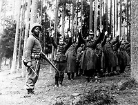 A Negro soldier of the 12th Armored Division stands guard over a group of Nazi prisoners captured in the surrounding German forest.  April 1945.  (OWI)<br /> Exact Date Shot Unknown<br /> NARA FILE #:  208-NP-6QQQ-1<br /> WAR &amp; CONFLICT BOOK #:  1282