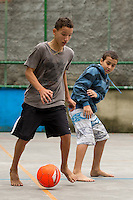 Kids play football in their bare feet at a small pitch in Favela Santo Amaro in the hills around Rio de Janeiro