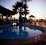 Reflections of silhouetted palm trees in resort pool at dusk. Tenerife, Canary Islands.