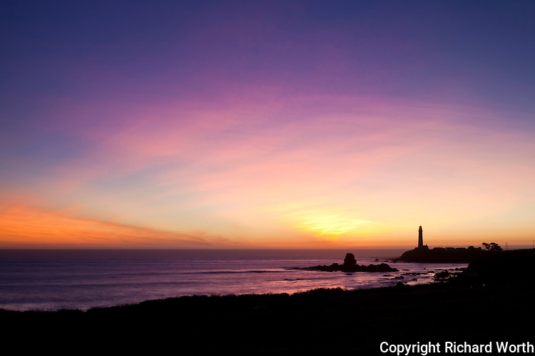 The light station, lighthouse, at Pigeon  Point stands in silhouette against a winter sunset on California's central coast.