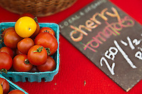 Red and yellow cherry tomatoes at a farmers market