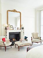 The master bedroom features a contemporary fireplace graced with a gilt-framed mirror