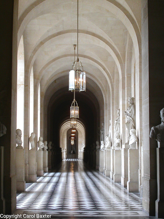 Afternoon sunrays illuminate a hallway lined with statues in the Chateau de Versailles, France - June 29, 2005.  The sunny black and white floor tiles bring attention to a small hallway that may otherwise have been missed by the visitor.