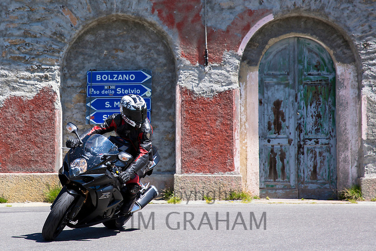 Motorcyclist on Suzuki R GSX motorbike drives The Stelvio Pass, Passo dello Stelvio, Stilfser Joch, to Bormio, Northern Italy