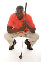 Casual young African American man in a bright orange golf shirt with a golf club lining up a putt.