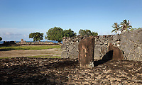 Standing stone or ofa 'i turui, representing the position of a god during ceremonies, by the ahu of Marae Taputapuatea, c. 1000 AD, a large religious and ceremonial temple site with a 60 x 45m stone courtyard and an ahu or altar made from 3m high standing stones cut from coral, at Taputapuatea, at Te Po, in the Opoa valley, on the island of Raiatea, in the Leeward Islands, Society Islands, French Polynesia. This marae marks the spot where Ta'aroa, creator and father of all Polynesian gods, first stepped on the earth. In the 17th century, it was rededicated to the god Oro, son of Ta'aroa and god of beauty, fertility and war. This site was a meeting place and sacrificial site for travellers from all over the Pacific. In the distance is Marae Hauviri or Marae Taura'a-a-tapu, family temple of Tamatoa, with the Te-Papa-tea-o-Ruea stone, brought by the god Hiro to found the chiefdoms or ari'i on Raiatea. Hauviri was the welcoming marae which received visitors as they disembarked from their canoes. Picture by Manuel Cohen