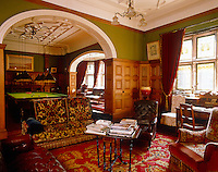 A panelled sitting room connects through an open archway to the billiard room