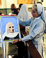 "A nurse holds a poster of the saint Laura of Saint Catherine of Siena known as ""Madre Laura"" at her mausoleum in Jerico, Colombia. May 12, 2013. Photo by Freddy Builes / VIEWpress."