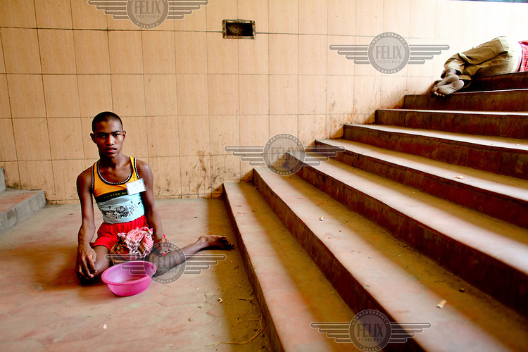 A man sits with his begging bowl at the bottom of a slight of stairs in an underpass.