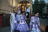 A group of women leave a venue after performering at a traditional Kazakh wedding.
