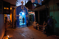Evening prayers at a small Catholic shrine on Ratnam Road during the Buddhist festival of Vesak at Ratnam Road in Colombo. A buddhist family lives to the right of the shrine. A multi racial/multi religious community in the North of Colombo.