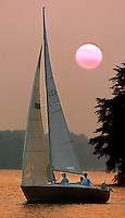 A sailboatcruises in the evening light on Lake Norman in NC.