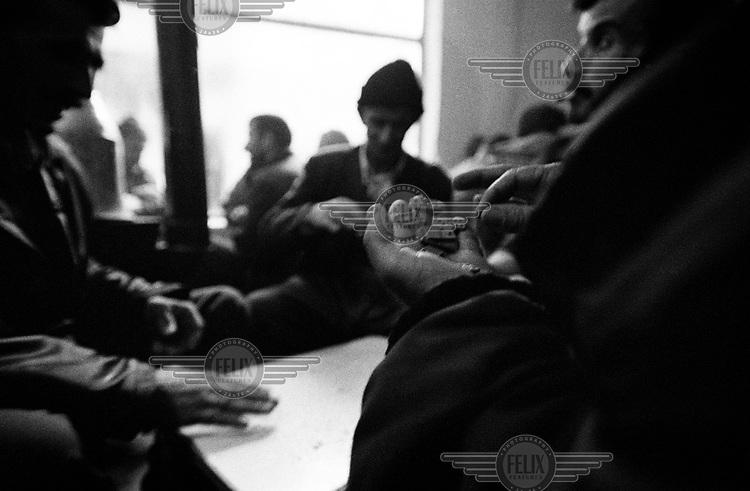 Men playing dominoes in a tea shop.