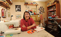 NWA Democrat-Gazette/ANDY SHUPE<br /> April Rusch, a trust officer with Arvest Assessment Management and a member of the Shiloh Museum of Ozark History's board of directors, enjoys sewing in her sewing room in her Fayetteville home.