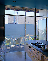 A glazed wall opens this contemporary kitchen to the terrace outside