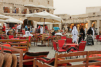 """.Doha, Qatar.  Entrance to the Recently Modernized """"Traditional"""" Market.  An Arab coffee shop is on the left.  A veiled Qatari woman in an abaya pushes a baby stroller (pram) on the right."""