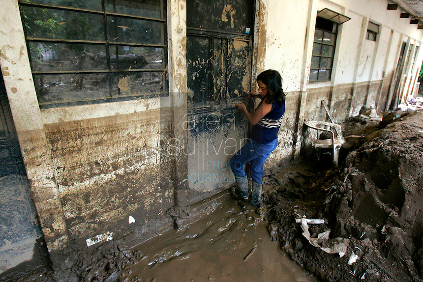 Carolina de Rosales enters her family's home, damaged by about four feet of mud, to check on its soiled contents. In early October a nearby river sent torrents of water and mud through the town, which sits near Antigua, and destroyed several homes after rains associated with Hurricane Stan inundated parts of Central America. Torrential rains and mudslides killed or made missing thousands of Guatemalans in early October.<br />