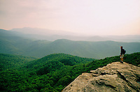 A hiker stands at the edge of a rock outcropping to take in the beautiful view of the Mountains and Valley in the Linville Gorge area of North Carolina.