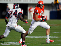 Virginia Cavaliers fullback Zachary Swanson (49) runs past Richmond Spiders defensive back Aaron Roane (24) during the second half of an NCAA football game Saturday September, 1, 2012 at Scott Stadium in Charlottesville, Va. Virginia defeated Richmond 43-19.